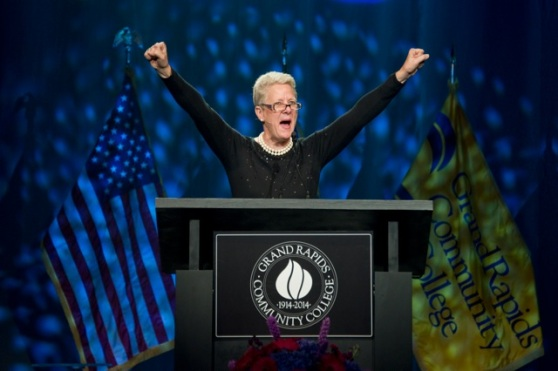 """A woman stands behind a lectern that says """"Grand Rapids Community College""""; her hands are raised in the air."""