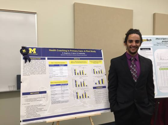 A young man in a suit and tie stands next to a poster board on an easel. The poster board, featuring the University of Michigan's maize and blue colors, is titled: Health Coaching in Primary Care: A Pilot Study.