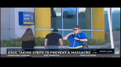 "A television screen shows students walking past the Campus Police station. Underneath it says: ""Top Stories. GRCC taking steps to prevent a massacre."""
