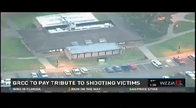 A television screen shows a large building; text underneath says: GRCC to pay tribute to shooting victims. WZZM 13.