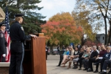 A man in a police uniform stands behind a lectern; people sit in chairs facing him. Everyone is outside.