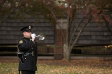 A man in a formal police uniform plays a bugle.