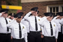 Police Academy cadets salute; they are outside.