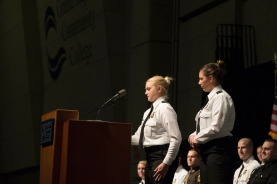 Two young women in police cadet uniforms stand behind a lectern. Other people in uniform are seated behind them.