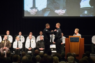 A man in a police uniform pins something to the shirt of a young man in a similar uniform. They stand on a stage; People in cadet uniforms and other law-enforcement uniforms are seated behind them. A woman stands behind a lectern.