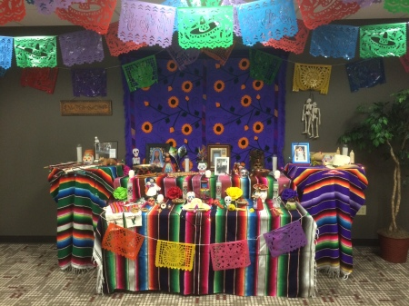 Photos, candles and figurines are set up on a grouping of three tables covered with striped cloths.