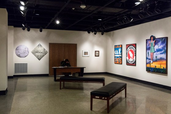 Paintings and drawings line the walls of a one-room gallery.