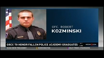 A television screen shows a photo of a police officer: GRCC to honor fallen Police Academy graduates. Ofc. Robert Kozminski.