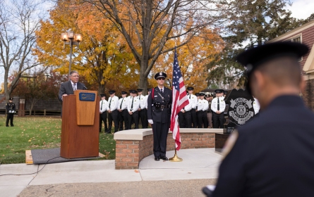 President Steven C. Ender delivers a speech behind a lectern. A man in a formal police uniform stands at attention with an American Flag next to a memorial. Cadets stand at attention behind them.