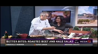 A man in a chef jacket prepares a salad as a woman watches.