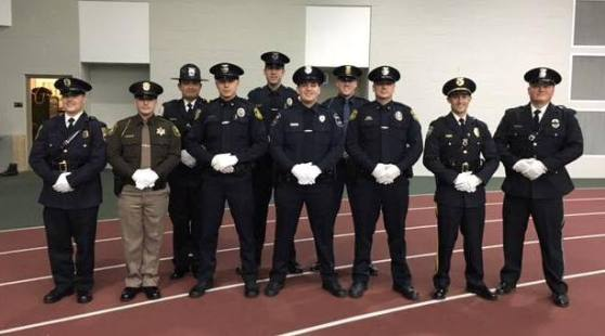 Ten men, all wearing different police uniforms, stand in a row in Ford Fieldhouse.