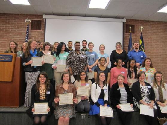 Phi Theta Kappa members stand and sit in rows, holding their certificates.