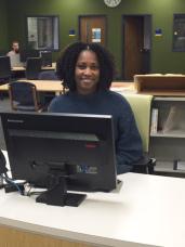 A woman sits at a desk behind a computer monitor.