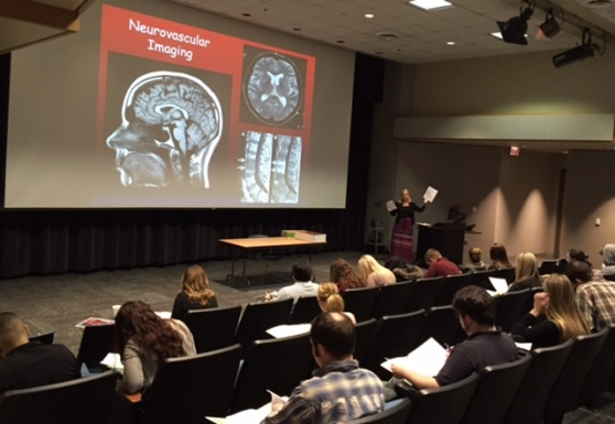 """A woman stands on a stage next to a lectern. A video screen shows MRI images and is labeled """"Neurovascular Imaging."""" Students are seated in the audience."""