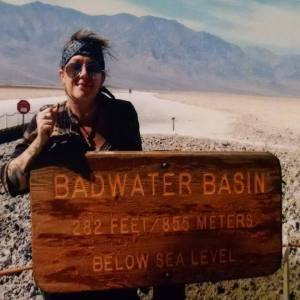 "Sarah Barker stands behind a sign that says: ""Badwater Basin. 282 feet/855 meters below sea level."""