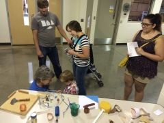 A group of people, including a little boy, are at a GRCC table at the Maker Faire.