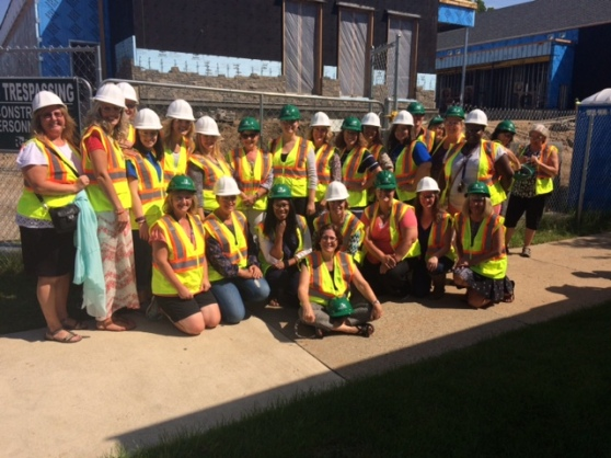Twenty-six people, all wearing hard hats and safety vests, stand in front of the laboratory preschool's construction site.
