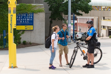 Two students talk to a Campus Police officer on a bicycle near Cook Hall.