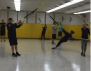 People are suspended by TRX equipment in the fieldhouse.