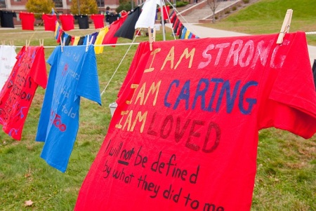 "T-shirts hang outdoors on a clothesline. One says: ""I am strong. I am caring. I am loved. I will not be defined by what they did to me."""