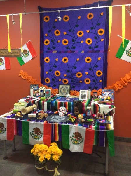 "A ""Dia de los Muertos"" altar is decorated with Mexican flags, skull figures and cards."
