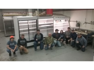 HVAC students crouch in front of installed supermarket display cases.
