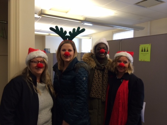 Four carolers wear santa hats or antlers and red noses.