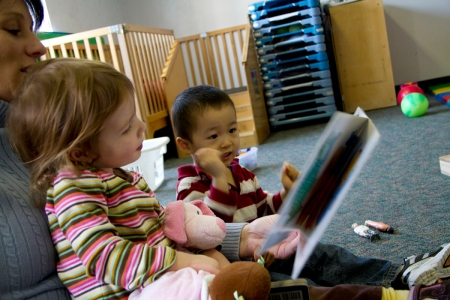 A woman reads a storybook to two preschoolers.