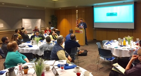 """Jesse Bernal of GVSU talks to tables of GRCC faculty and staff. The video screen behind him says: """"Why diversity?"""""""