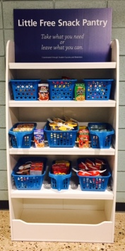 Baskets of snacks sit on shelves. A sign on top says: Little Free Snack Pantry. Take what you need or leave what you can. College Success and Retention Center.