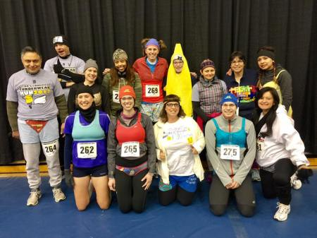 Thirteen of 14 faculty members wear underwear over their running clothes. The 14th is dressed as a banana.