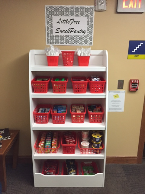 """Snacks are stored in plastic baskets on the shelves of a small storage unit. A sign above it says: """"Little Free Snack Pantry."""""""
