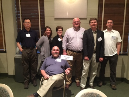 """Steve Abid sits in a chair. Standing behind him are Yan Bai, Heather Richards, Laurie Chesley, Gordan Vurusic, Mike Vargo and Dillon Carr. A sign that Abid holds says: """"GRCC Raiders."""""""