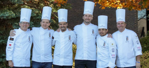 Six chefs stand outside near trees.