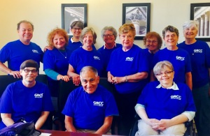 Two men and 12 women, all wearing GRCC T-shirts, sit and stand by a conference table.