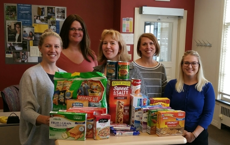 Leah Nixon, Amanda Kossack, Julia Yob, Malinda Powers and Leigh Jajuga stand behind a table with boxes and bags of snack.