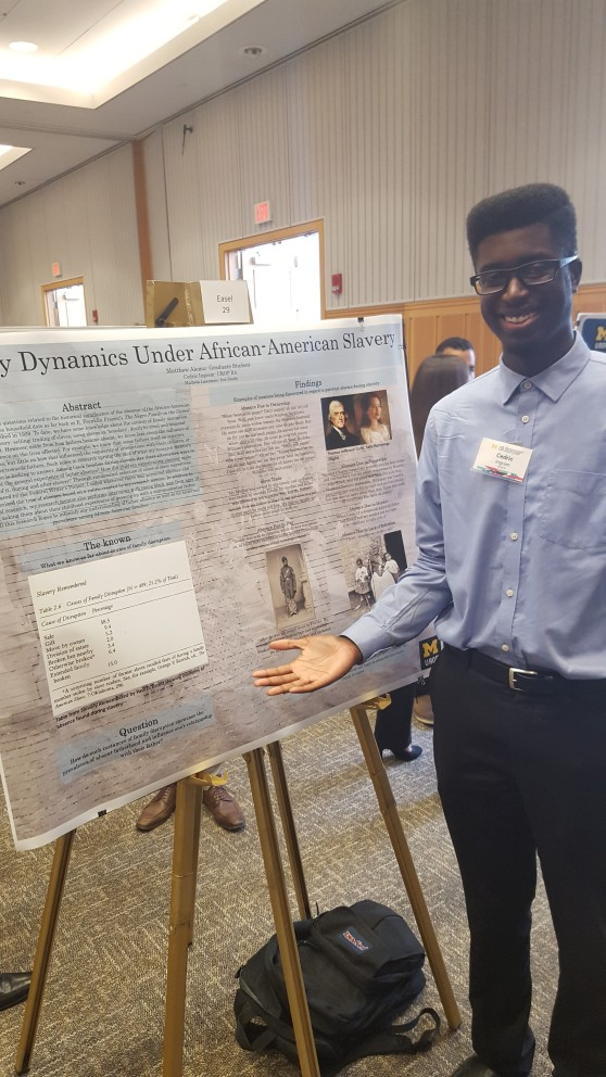 """Cedric Ingram stands next to his poster on """"Family Dynamics Under African-American Slavery."""""""