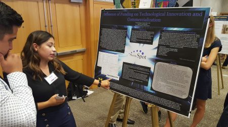 "Chantal Garcia points to something on her poster for ""Influence of Funding on Technological Innovation and Commercialization."" A man stands next to her, looking at the poster."