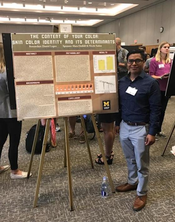 """Daniel Lopez stands next to his poster of """"The Content of Your Color: Skin Color Identity and Its Determinants."""""""