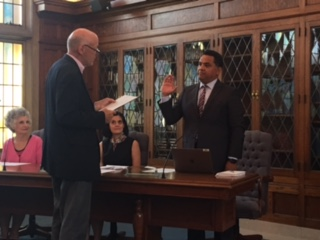 David J. Koetje swears in Carlos Sanchez in the boardroom.
