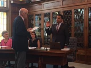 David J. Koetje swears in Carlos Sanchez in the boardroom.