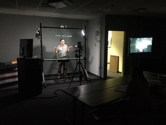 Bill Faber talks to a camera as he stands behind a lightboard.