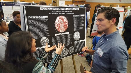 "Maleny Crespo stands next to his poster on ""Political Sprituality of Latinx Culture."" A woman is talking to him."