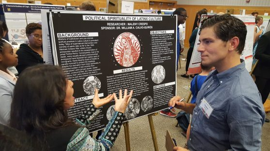 """Maleny Crespo stands next to his poster on """"Political Sprituality of Latinx Culture."""" A woman is talking to him."""