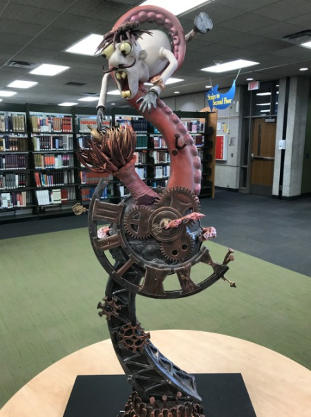 A chocolate sculpture, depicting a man wrapped in a tentacle on top of clockworks, sits in the library.