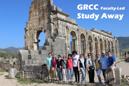 "Photo of group posing near ruins. The text says ""GRCC Faculty-Led Study Away"""