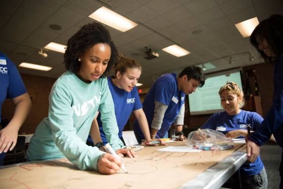 Honors program students write on a long piece of paper on a table.
