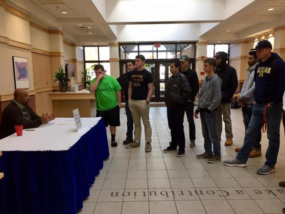 A man representing Alternative Directions sits behind an information table in Sneden's lobby. Criminal Justice students stand on the other side of the table.
