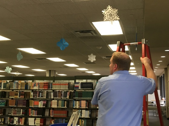 Jason Natte stands by a ladder in the library; paper snowflakes hang from the ceiling.