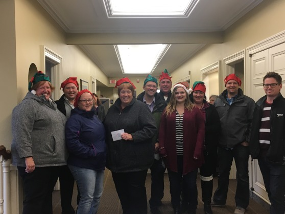 Five women and five men, many wearing elf hats, sing in the hallway by the president's office in the Administration Building.